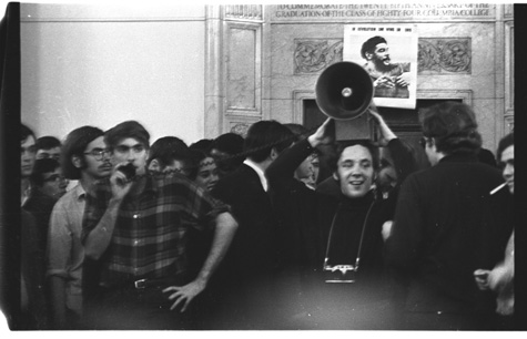 A young Mark Rudd speaking into a microphone at a rally with a portrait of Che Guevara in the background.