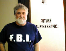 Mark Rudd wearing an F.B.I. t-shirt and standing in front of a door with the words 'Future Business Inc' printed on it.