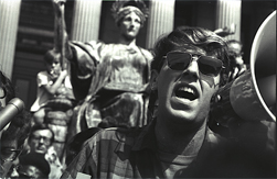 A young Mark Rudd wearing sunglasses and yelling into a megaphone.